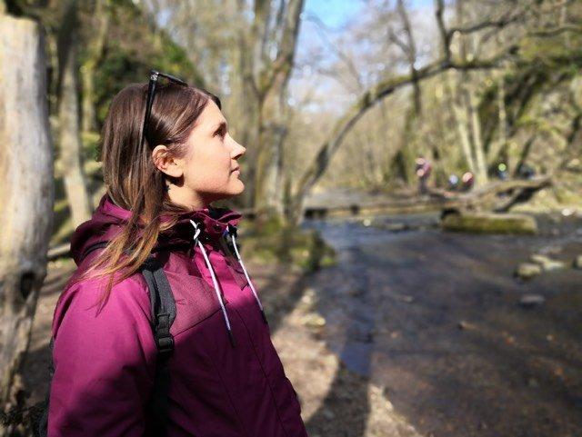 dívka se dívá do nebe uprostřed lesa u vody